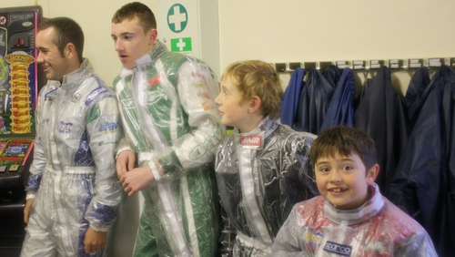 Drivers waiting for their briefing wearing transparent wet suits over their racing suits
