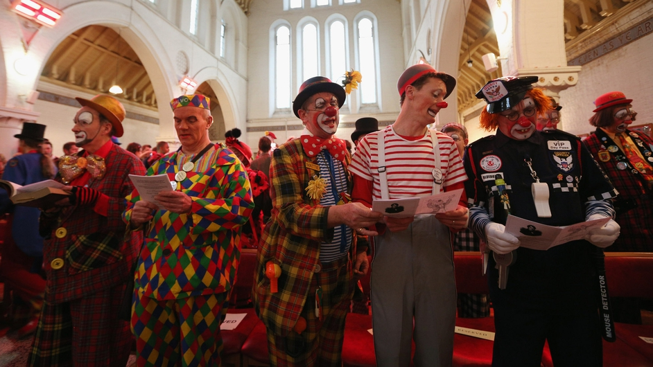 Clowns in full costume sing during the annual Clowns Church Service at Holy Trinity Church in Dalston