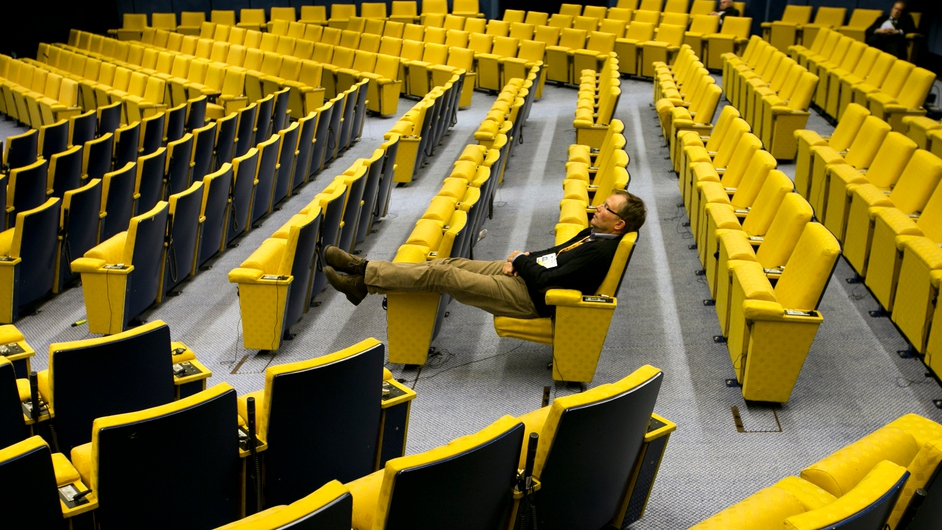 A man sits in the near-empty main hall at EU headquarters