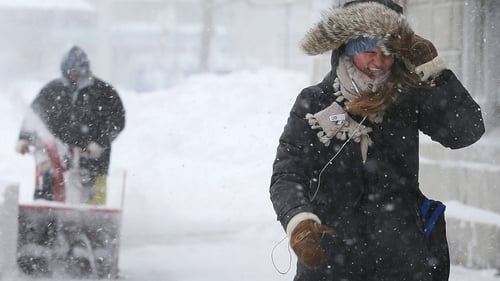A woman walks through the snow  during a lingering blizzard in Boston