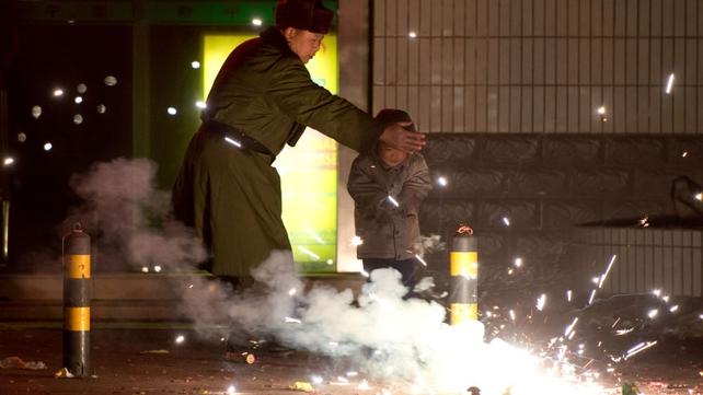 A man shields a boy from firecrackers on a street in Beijing