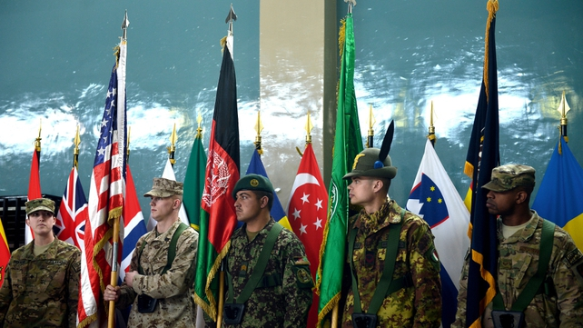 An Afghanistan National Army soldier and ISAF soldiers hold flags during a change of command ceremony