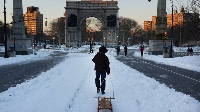 A boy pulls a sled through a snowy Prospect Park in Brooklyn