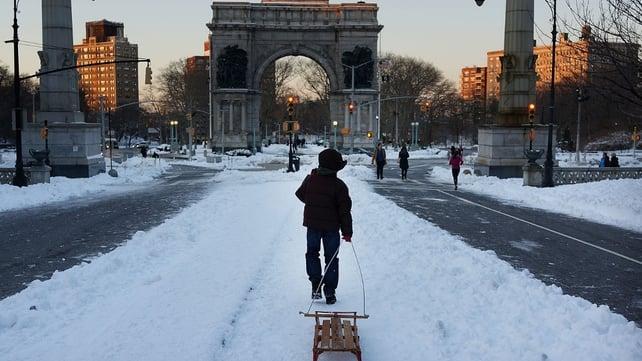 A boy pulls a sled through a snowy Prospect Park in Brooklyn