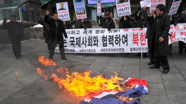 Anti-North Korea activists burn a North Korean flag at a protest in Seoul