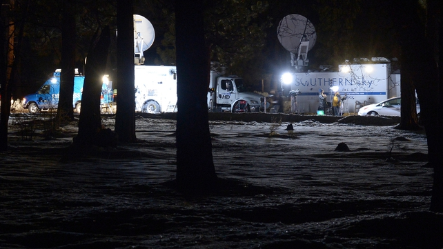Satellite trucks stand parked at a roadblock on Highway 38