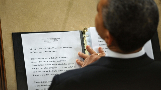 Mr Obama rests his hands on a copy of his speech as he delivers his address