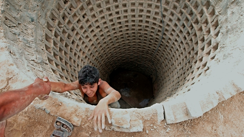 A Palestinian man helps a smuggler to ascend a tunnel along the Gaza-Egypt border in Rafah, in southern Gaza
