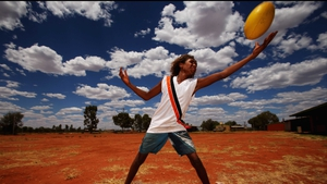 A boy catches an Australian rules football as the Indigenous All Stars visit Yuendumu School in the Australian outback