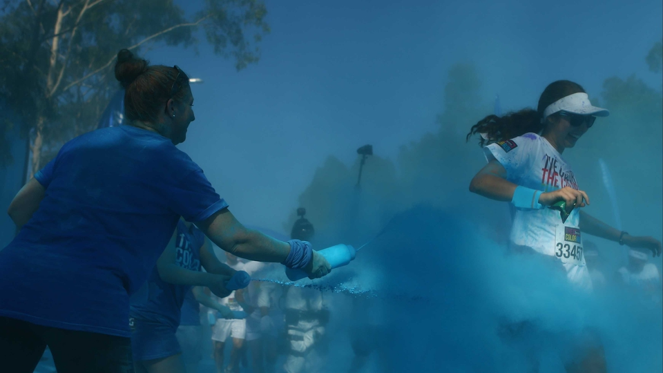 Runners pass through the blue colour throw area at the Colour Run in Sydney