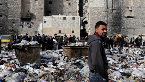 People pictured in a bazaar next to a rubbish heap in the northern city of Aleppo