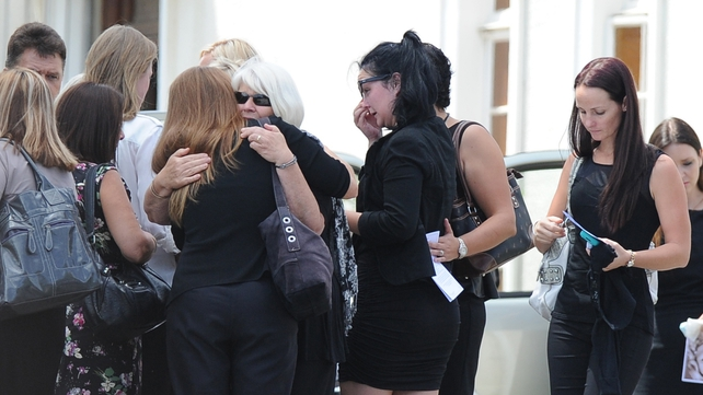 Ms Steenkamp's family and friends embrace after the service