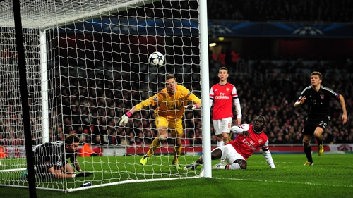 Wojciech Szczesny of Arsenal scrambles in vain to prevent the ball crossing the line as goalscorer Mario Mandzukic of Bayern Munich watches from inside the goal