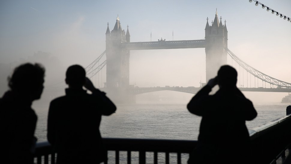 People look and photograph Tower Bridge as it emerges from early morning fog on The River Thames in London, England