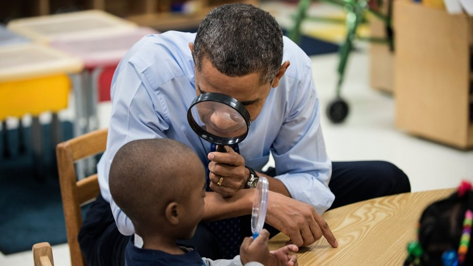 US President Barack Obama looks at a boy with a magnifying glass while visiting children at College Heights Early Childhood Learning Center