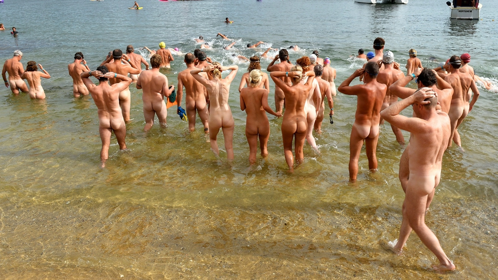 The first wave of nude swimmers enter the surf in the 'Sydney Skinny' - in what is dubbed the first mass nude ocean swim in Sydney