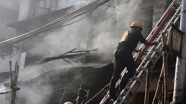 Indian firefighters climb a ladder as they attempt to control a blaze in the Surya Sen market building in Kolkata