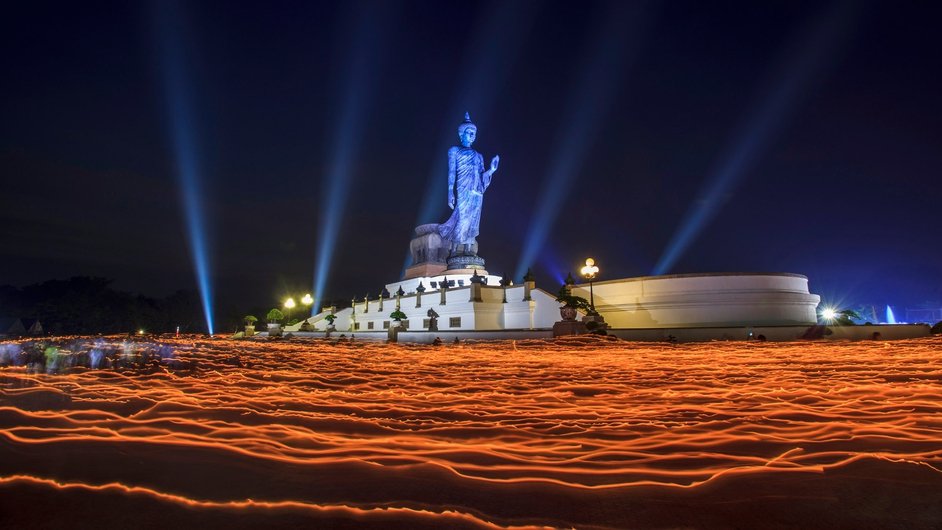 People walk around the Buddha statue holding candles for prayers during Makha Bucha Day at Buddhist Park in Nakhon Pathom, Thailand