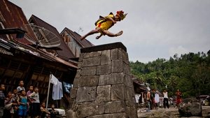 A villager wearing traditional costume jumps over a stone in Orahili Fau village on Nias Island, Indonesia