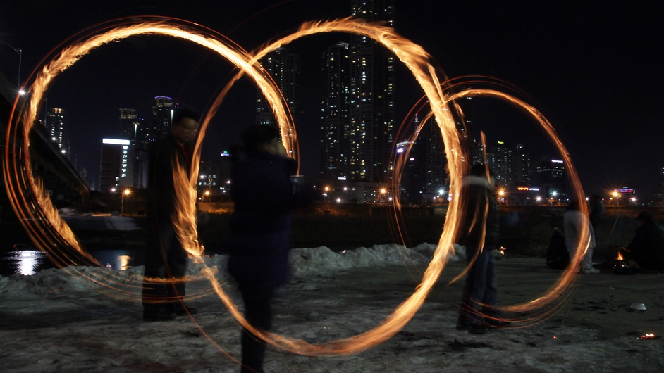 Koreans spin fire cans during a folk game at Han River in Seoul, as part of a holiday to celebrate the first full moon of the lunar new year