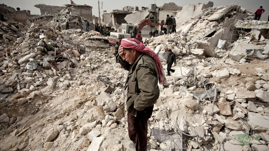 A Syrian man stands on the rubble of his house while others look for survivors and bodies in the Tariq al-Bab district of Aleppo