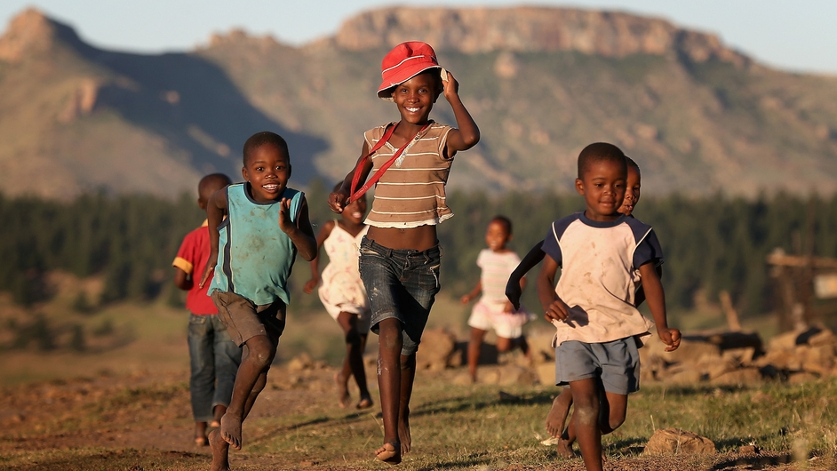 Children run towards charity workers from Sentebale in Morija, Lesotho