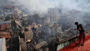A resident looks at destroyed houses after a fire engulfed a slum area in Manila