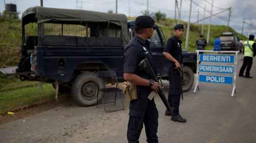 Malaysian police man a security checkpoint in Cenderawasih, Borneo