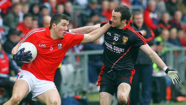 Cork's Thomas Clancy holds off the challenge of Down's Conor Laverty