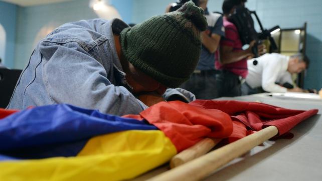 A supporter signs a condolences book in Tegucigalpa, Honduras