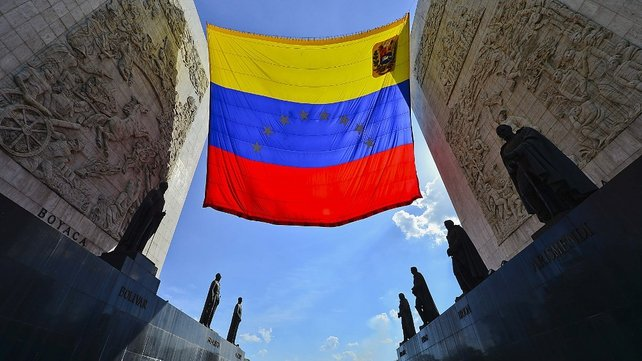 The Venezuelan flag flies over the Monument to the Founding Fathers at the entrance to the military academy