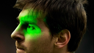 Barcelona's Lionel Messi is illuminated by laser during the la Liga match between Real Madrid and Barcelona at the Bernabeu