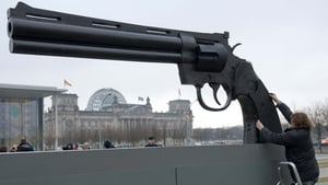 Activists place an oversized gun in front of the Federal Chancellery in Berlin, with the writing 'Our weapons kill, Germany is the third largest weapons exporter in the world'