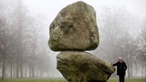 Artist Peter Fischli poses next to 'Rock on Top of Another Rock', in Hyde Park in London