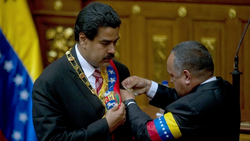President of the Venezuelan National Assembly Diosdado Cabello puts the presidential sash on Venezuelan Vice President Nicolas Maduro