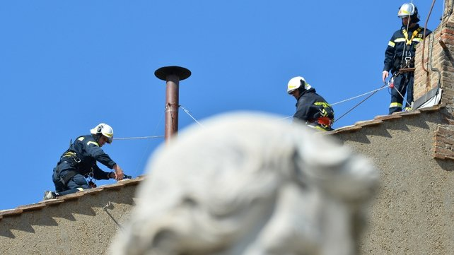 Vatican firefighters set up the chimney on the roof of the Sistine chapel