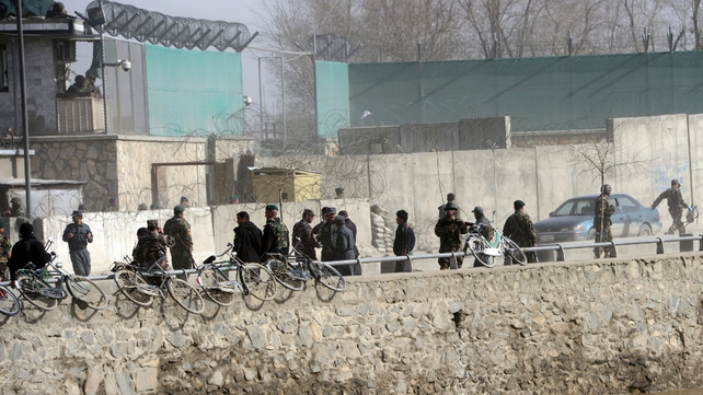 Soldiers and security personnel walk at the site of a suicide attack next to the ministry of defence main gate in Kabul