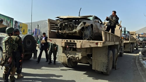 Afghanistan National Army soldiers remove a destroyed car at the site of a suicide attack in Kabul