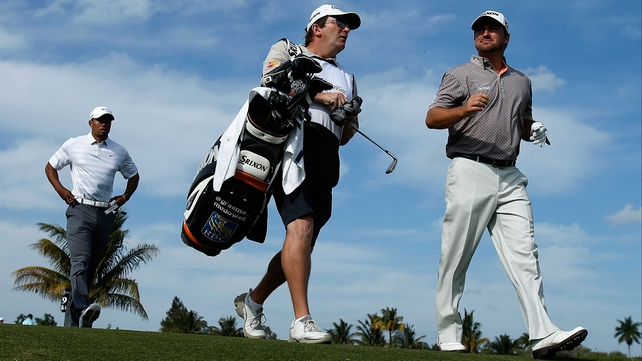Graeme McDowell walks alongside his caddie Ken Comboy as Tiger Woods follows