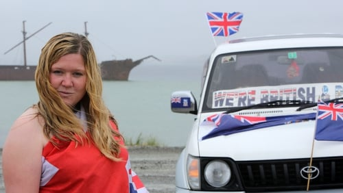 Falkland Islander Sam Davies beside posters calling to vote yes to remain British in the referendum