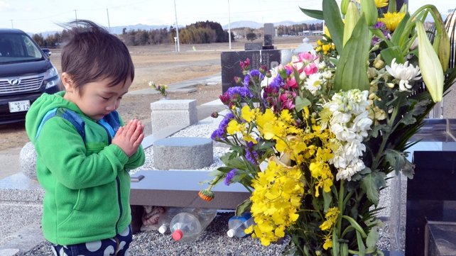 A little boy prays for his relatives killed by the 2011 tsunami at a cemetery in Minamisoma in Fukushima