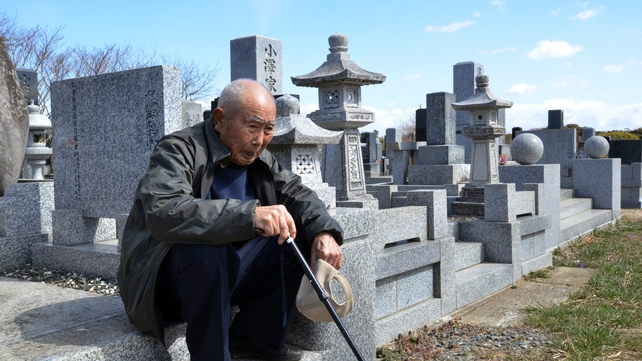 An elderly man visits a cemetery to pay respects to his son who was killed in the tsunami in Minamisoma in Fukushima prefecture