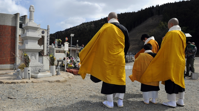 A group of Buddhist monks recites the sutra at the memorial alter at the Okawa elementary school