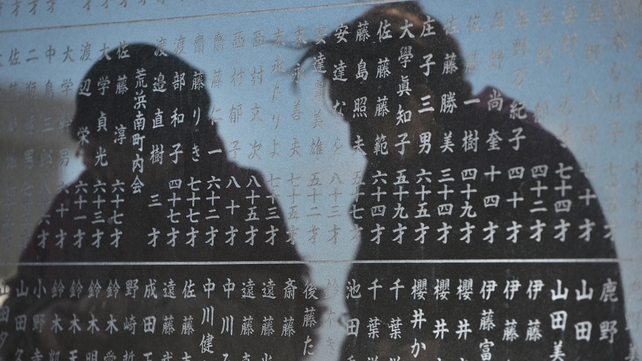 Two elderly women are reflected on a monument on which names of tsunami victims from the district are carved in Arahama district in Sendai, Miyagi Prefecture