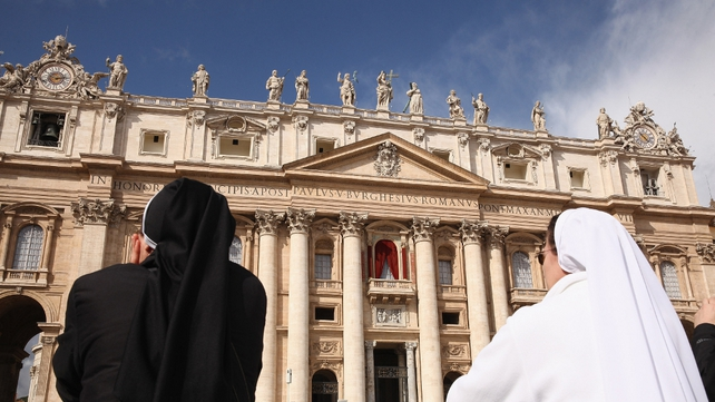Nuns pray in front of St Peter's Basilica in St Peter's Square