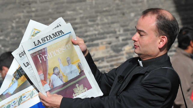 A priest shows front pages of newspapers with pictures of the new pope, Pope Francis