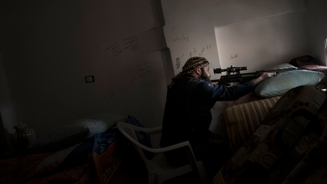 A rebel sniper takes aim at government forces with his Dragunov SVD rifle from a house in the Syrian eastern city of Deir Ezzor