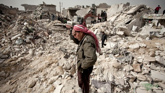 A Syrian man stands on the rubble of his house while others look for survivors and bodies in Aleppo
