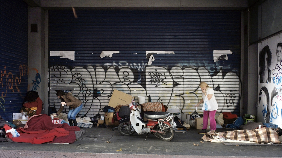 Local shop workers bring hot drinks to homeless people sleeping on Athens' Panapestimou Street