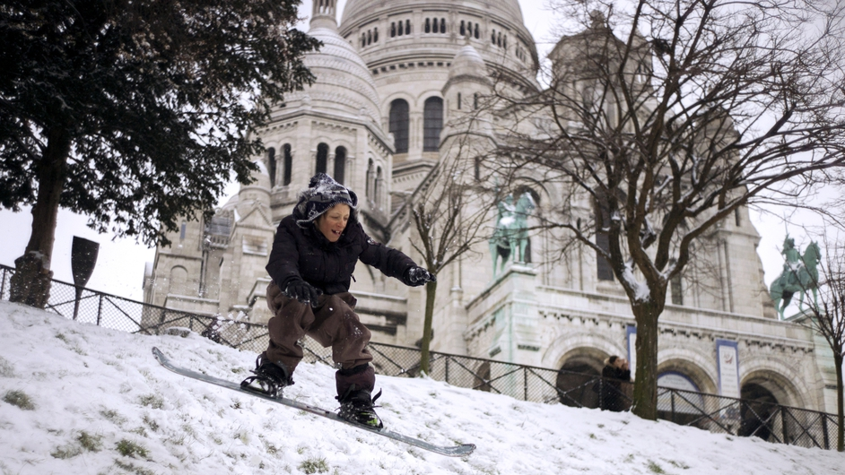 A child slides on a snowboard in front of the snow-covered Sacre-Coeur Basilica in Montmartre, Paris